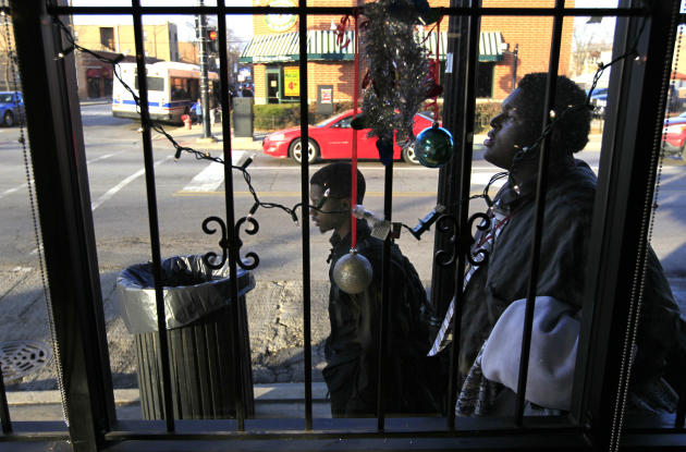 In this Monday, Dec. 3, 2012 photo, two boys walk past Christmas decorations in the barred window of a business along 79th Street in the Auburn-Gresham neighborhood on Chicago's South Side. The violen