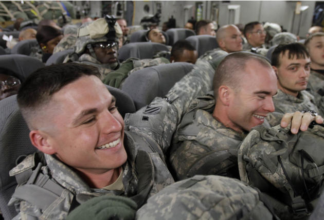In this Dec. 2, 2010 photo, U.S. Army soldiers from 1st Brigade, 3rd Infantry Division, based at Fort Stewart, Ga., react while seated in the belly of a C-17 aircraft at Sather Air Base in Baghdad as