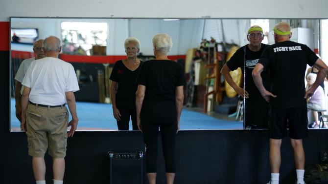 Parkinson's patients Jim Coppula, Deloris Nouhan and Ron Addison greet themselves and work on their posture as they train during their Rock Steady Boxing class in Costa Mesa California