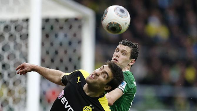 Dortmund's Sokratis of Greece, left, an Bremen's Zlatko Junuzovic of Austria challenge for the ball during the German first division Bundesliga soccer match between Werder Bremen and Borussia Dortmund in Bremen, Germany, Saturday, Feb. 8, 2014