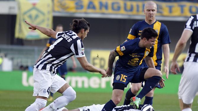 Verona's Juan Manuel Iturbe, right, of Paraguay, is challenged by Juventus' Giorgio Chiellini, bottom, and teammate Martin Caceres, left, of Uruguay, during a Serie A soccer match at Bentegodi stadium in Verona, Italy, Sunday, Feb. 9, 2014
