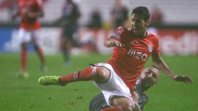 Benfica's Andre Almeida, front, is tackled by Olympiacos' Kostas Mitroglou during the Champions League group C soccer match between SL Benfica and Olympiacos FC in Lisbon, Wednesday, Oct. 23, 2013. The game ended in a 1-1 draw