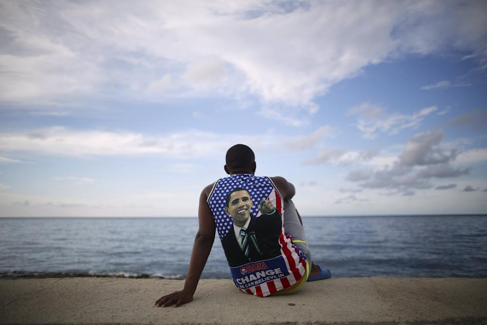 Medical student Electo Rossel, 20, wearing a shirt with a picture of U.S. President Obama, listens to music at the Malecon seafront outside the U.S. embassy in Havana, Cuba