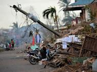 Children walk near a toppled electricity post in Boston town, Davao Oriental province on December 10, 2012. The death toll from the strongest typhoon to hit the Philippines this year has climbed above 900, with hundreds still missing, the government said