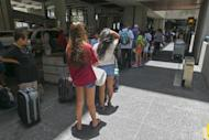Crowds line up outside the departures terminal at the Honolulu International Airport in Honolulu on Thursday, Aug. 7, 2014. With Iselle, Hawaii is expected to take its first direct hurricane hit in 22 years. Tracking close behind it is Hurricane Julio. Hawaiian Airlines announced Thursday they are waiving change fees for passengers trying to leave before the hurricanes hit the islands. (AP Photo/Marco Garcia)