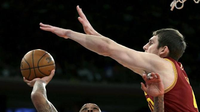 New York Knicks' Shannon Brown, left, puts up a shot while Cleveland Cavaliers' Tyler Zeller defends during the first half of an NBA basketball game at Madison Square Garden, Sunday, March 23, 2014, in New York