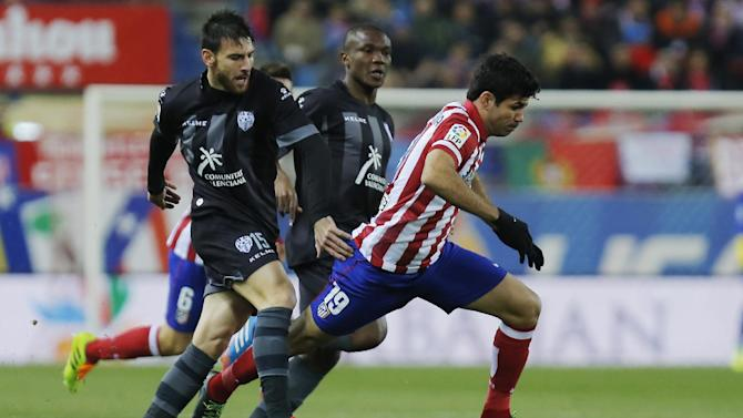 Atletico's Diego Costa, right, competes with Nikos Karampelas from Greece, left, during a Spanish La Liga soccer match between Atletico de Madrid and Levante at the Vicente Calderon stadium in Madrid, Spain, Saturday, Dec. 21, 2013