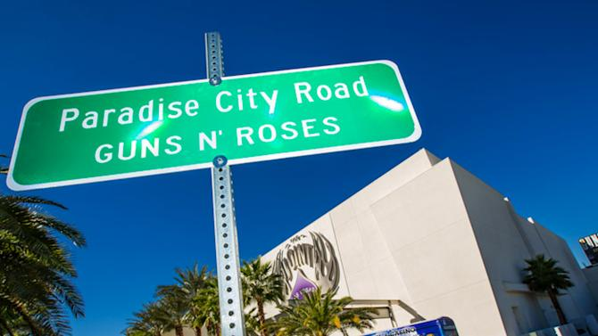 "This Monday Oct. 29,2012 photo provided by Erik Kabik shows the street sign after a ceremonial street renaming of Paradise Road to Paradise City Road in Las Vegas.  A county commissioner in Las Vegas says she regrets the board temporarily renamed a street in honor of Guns N' Roses after finding out about the band's suggestive publicity artwork. Ads promoting the band's four-week run at the Hard Rock Hotel & Casino depict a disheveled woman who appears to be sexually assaulted beneath the iconic ""Welcome to Fabulous Las Vegas"" sign. (AP Photo/Courtesy Erik Kabik)"