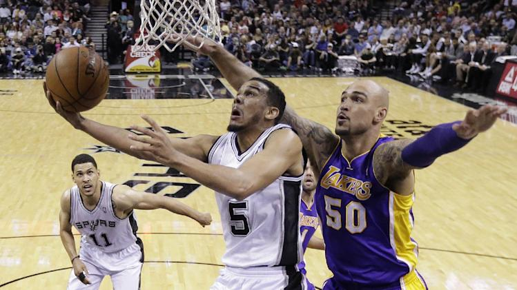 San Antonio Spurs' Cory Joseph (5) is pressured by Los Angeles' Robert Sacre (50) as he tries to score during the second half of an NBA basketball game, Wednesday, April 16, 2014, in San Antonio. Los Angeles won 113-100