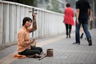 A blind woman plays an erhu instrument as she busks on a street in Beijing. Chinese Premier Wen Jiabao said Sunday that the country's economy faces downward pressure as he called for more aggressive moves to keep growth on track, state media reported