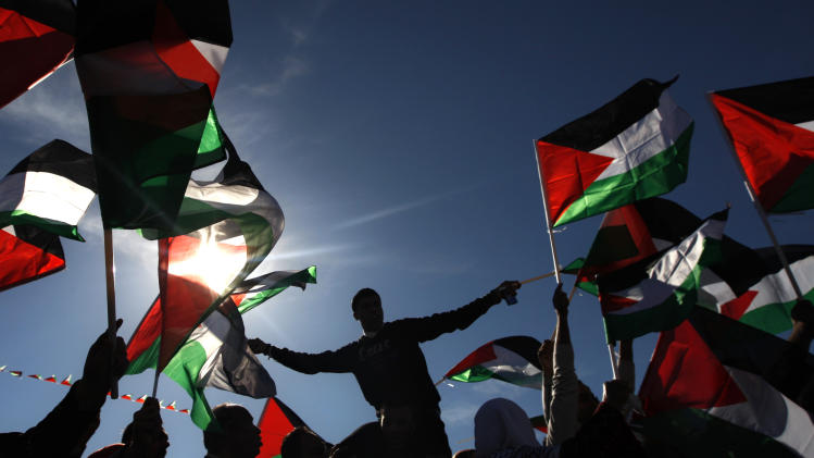 Palestinians wave flags as they celebrate their successful bid to win U.N. statehood recognition in the West Bank city of Ramallah, Sunday, Dec. 2, 2012. Palestinian President Mahmoud Abbas returned home to a hero's welcome after winning a resounding endorsement for Palestinian independence at the United Nations. Israel on Sunday roundly rejected the United Nations' endorsement of an independent state of Palestine, announcing it would withhold more than $100 million collected for the Palestinian government to pay debts to Israeli companies. (AP Photo/Majdi Mohammed)