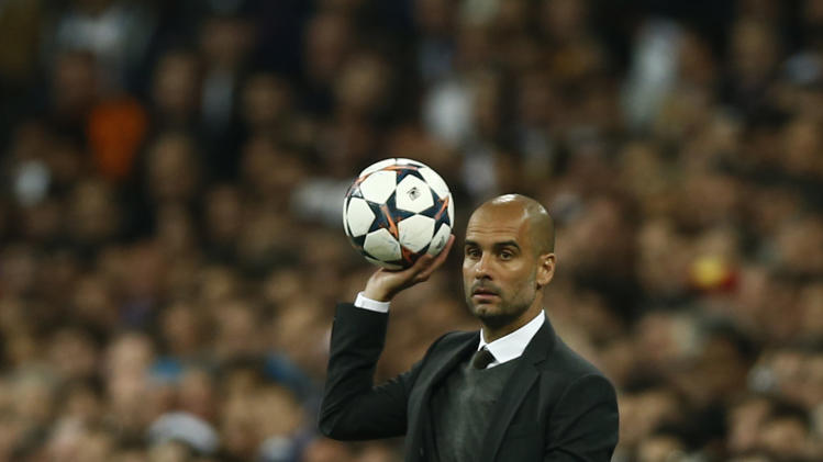 Bayern head coach Pep Guardiola, holds the ball during a first leg semifinal Champions League soccer match between Real Madrid and Bayern Munich at the Santiago Bernabeu stadium in Madrid, Spain, Wednesday, April 23, 2014
