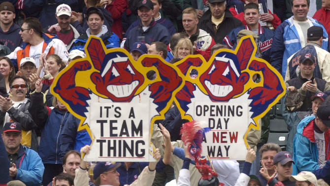 FILE  - In this April 8, 2002 file photo, fans hold up Chief Wahoo logo signs as they celebrate the Cleveland Indians' opening win over the Minnesota Twins in Cleveland, Ohio. Many experts say using any human being as a mascot is demeaning regardless of the depiction, though communities at times have been reluctant to cede old traditions. The team continues to use the image of Chief Wahoo despite criticism from those who find it offensive