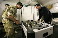 """British Prime Minister David Cameron (R) plays table football with a Royal Marine during a visit to Forward Operating Base Price in Helmand Province, Afghanistan, on December 20, 2012. During his visit, Cameron insisted that the """"high price"""" paid by servicemen has been worthwhile"""