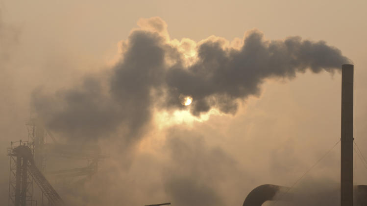 "FILE - Smoke pours from a chimney at a cement plant in Binzhou city, in eastern China's Shandong province, Thursday, Jan. 17, 2013. Scientists from around the world have gathered in Stockholm in September 2013 for a meeting of a U.N. panel on climate change and will probably issue a report saying it is ""extremely likely"" - which they define in footnotes as 95 percent certain - that humans are mostly to blame for temperatures that have climbed since 1951. (AP Photo)"