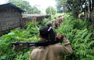 Indian security personnel patrol at Dangtol village, in Chirang District. Indian police recovered 12 bodies from rice fields and roadsides in the remote state of Assam on Wednesday as the death toll from ethnic violence rose to 38 after four days of bloody clashes