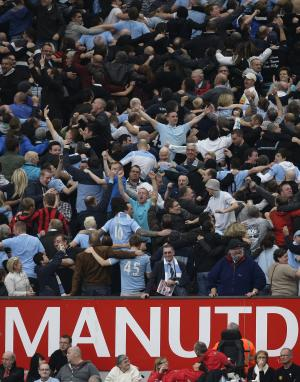 Manchester City supporters celebrates as their team beat Manchester United 6-1 in their English Premier League soccer match at Old Trafford Stadium, Manchester, England, Sunday Oct. 23, 2011. (AP Photo/Jon Super)