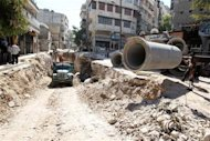 Workers install pipes along a street in Aleppo September 9, 2013. REUTERS/Muzaffar Salman