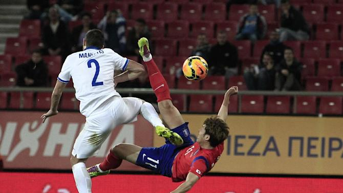 Greece's Giannis Maniatis, left, tries to stop South Korea's Son Heungmin as he shoots a cross kick during a friendly match at Georgios Karaiskakis stadium in Piraeus port, near Athens, Wednesday, March 5, 2014