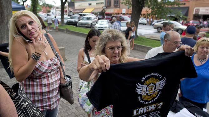 Julie Rockwell looks over a T-shirt to buy honoring the 19 fallen Granite Mountain Hotshot firefighters, Friday, July 5, 2013, in Prescott, Ariz. After an out-of-control blaze killed all but one of the Hotshot crew, Sunday, city residents and tourists flocked to the booth at the Courthouse Plaza to buy shirts to help raise money for the Hotshots' families. (AP Photo/Julie Jacobson)