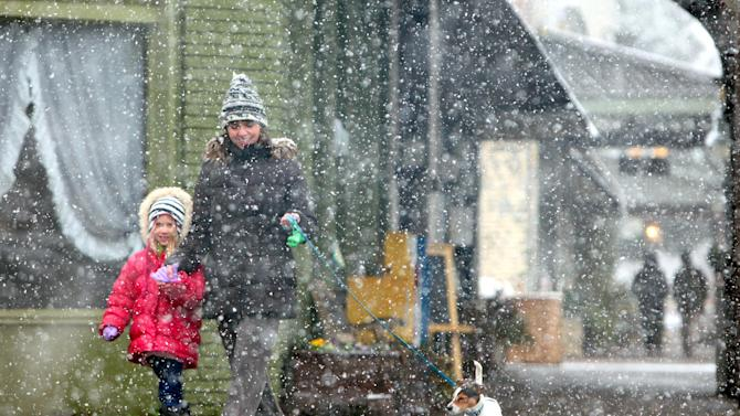 Ember Pedersen, 6, left, Lani Pedersen and their dog Tucker walk along Main Ave. in historic downtown Northport, Ala. Thursday, Jan. 17, 2013. A wet blanket of snow covered much of West Alabama Thursday morning.   (AP Photo/The Tuscaloosa News,Dusty Compton )