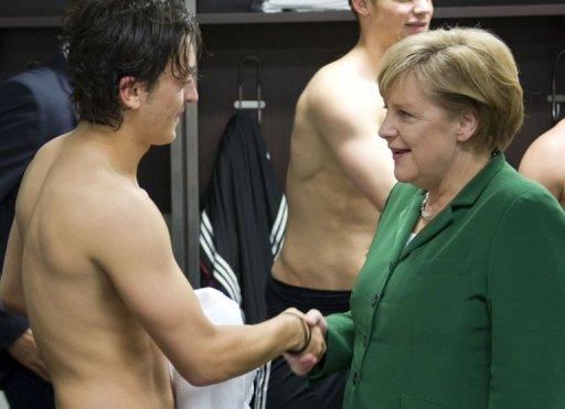 Merkel congratulates Germany's Mesut Ozil after a Euro 2012 qualifier in Berlin in 2010
