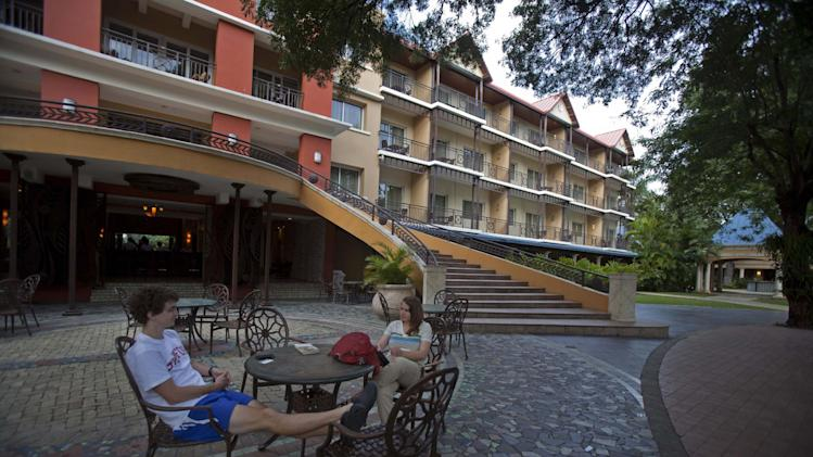 "In this July 3, 2013 photo, tourists Kevin Bagley, left, and Meg Quinn, sit in the Karibe Hotel courtyard during their six day visit, in Port-au-Prince, Haiti. The Haitian government is trying to revive the country's long stagnant tourism industry with plans that include making use of a little-known ""investment code"" that gives 15-year tax breaks to the owners of new hotels, many of whom are from the country's powerful and wealthy families. This law also allows hotel owners to ship supplies through customs without paying taxes. (AP Photo/Dieu Nalio Chery)"