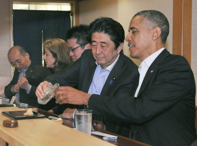 Japanese Prime Minister Shinzo Abe pours sake for U.S. President Barack Obama as they have dinner at the Sukiyabashi Jiro sushi restaurant in Tokyo
