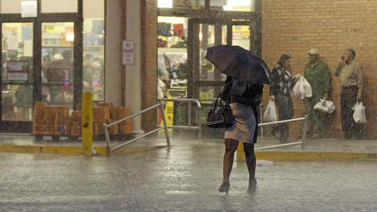 A woman walks through a heavy rain as others wait for the rain to stop at a grocery store in Montgomery, Ala., Monday, March 18, 2013. A line of severe thunderstorms crossed the state, bringing heavy rain and high winds. (AP Photo/Dave Martin)