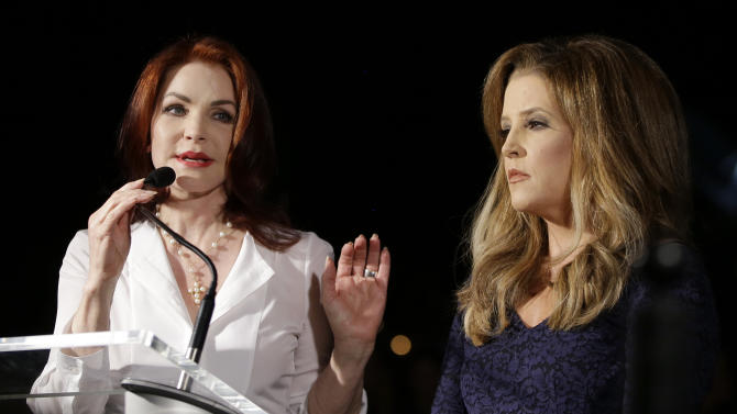Priscilla Presley, left, and Lisa Marie Presley speak to fans gathered at a candlelight vigil at Graceland, Elvis Presley's Memphis, Tenn. home, on Wednesday, Aug. 15, 2012. Fans from around the world are at Graceland to commemorate the 35th anniversary of Elvis Presley's death. (AP Photo/Mark Humphrey)