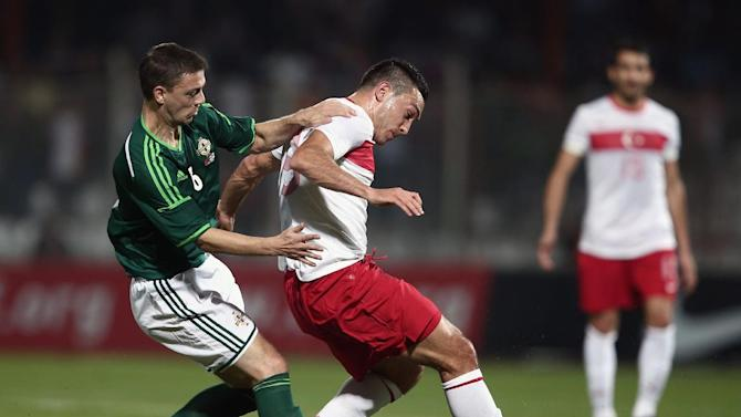 Turkey's Mevlut Erdinc, right, and Chris Baird of Northern Ireland fight for the ball during their friendly soccer match in Adana, Turkey,  Friday, Nov. 15, 2013.(AP Photo)