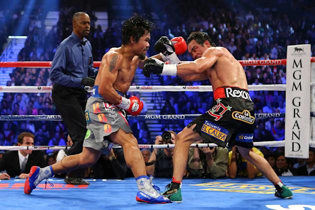 LAS VEGAS, NV - DECEMBER 08: (L-R) Manny Pacquiao throws a left at Juan Manuel Marquez during their welterweight bout at the MGM Grand Garden Arena on December 8, 2012 in Las Vegas, Nevada. (Photo by Al Bello/Getty Images)