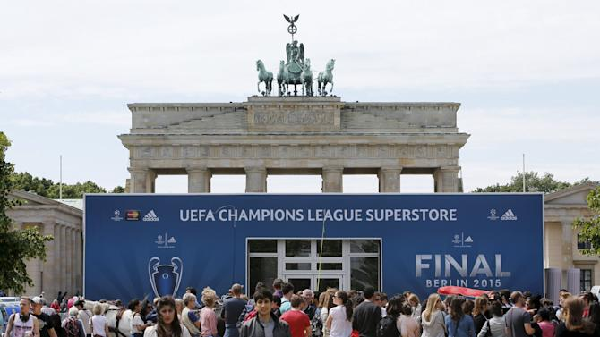 People walk in front of an advertising board for the UEFA Champions League final at the Brandenburg gate in Berlin