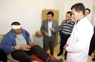 Chinese Ambassador to Zambia Zhou Yuxiao (C) visits a victim of the Collum Coal mine wages riot at Levy Mwanawasa Hospital on August 6, 2012 in Lusaka. The killing of a Chinese mine boss last weekend has left Zambian President Michael Sata's government rushing to reassure foreign investors on their safety