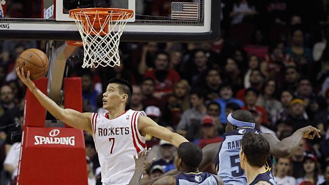 Houston Rockets guard Jeremy Lin (7) drives for a reverse layup past Memphis Grizzlies' Ed Davis (32) and Zach Randolph (50) during the first half of an NBA basketball game Thursday, Dec. 26, 2013, in Houston