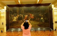 "A tourist takes a photograph of the restored painting ""Spoliarium"", at the National Museum in Manila in June 2011. Flash camera-toting tourists could wreck the Philippines' greatest work of art, say the worried curator of the ""Spoliarium"", a symbol of Filipino awakening against Spain's colonial yoke"