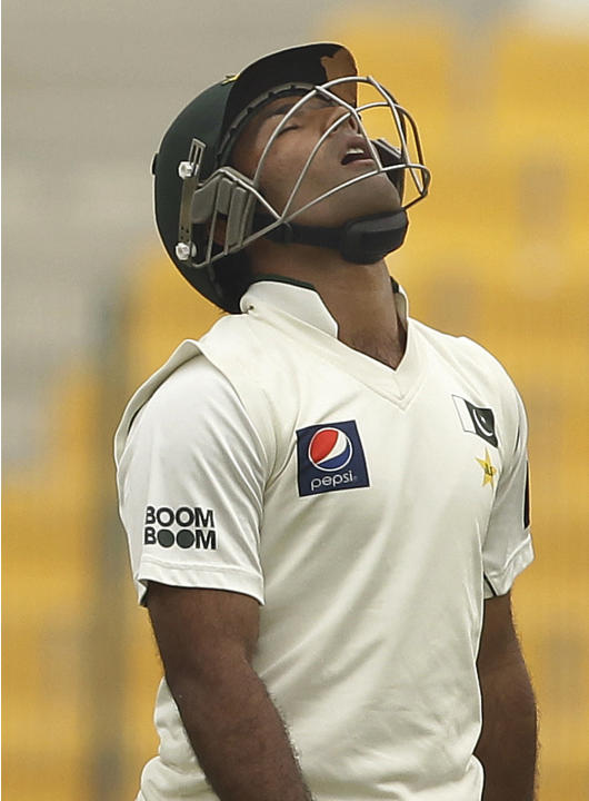 Pakistan's Asad Shafiq walks off the field of play after losing his wicket to England's Monty Panesar during the fourth day of the second cricket test match of a three-match series between England and