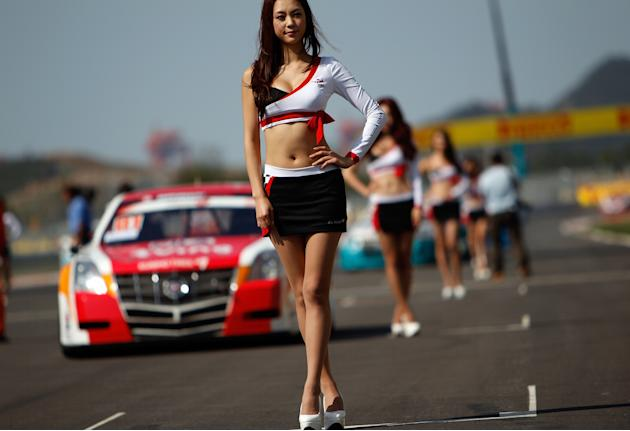 Grid girls stand in formation on the circuit prior to the start of the Formula One Korean Grand Prix in Yeongam on October 16, 2011. AFP PHOTO / SAEED KHAN (Photo credit should read SAEED KHAN/AFP/Get