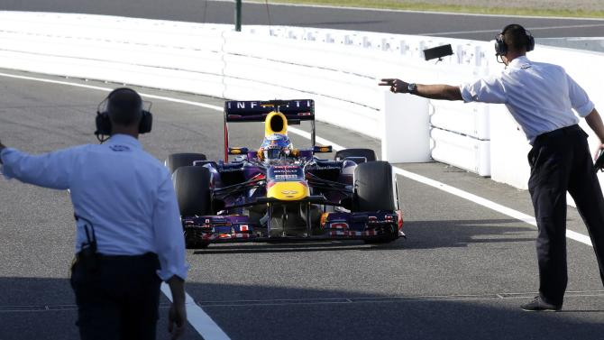 Red Bull Formula One driver Vettel of Germany is directed to the Parc Ferme after the qualifying session of the Japanese F1 Grand Prix at the Suzuka circuit