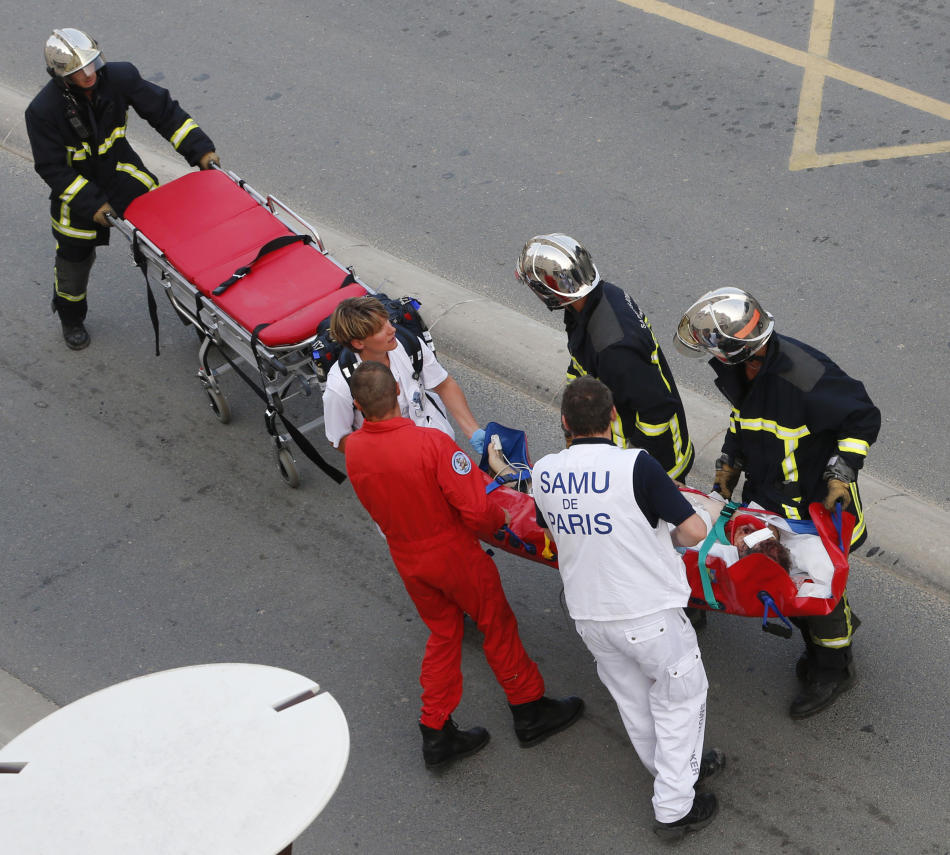 Rescue workers transport a victim from a train that derailed in Bretigny sur Orge, south of Paris, Friday July, 12, 2013. A packed passenger train skidded off its rails after leaving Paris on Friday,