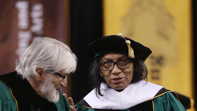 "Wayne State University Board of Governors Paul Massaron, left, talks with Sixto Rodriguez after Rodriguez received a Doctor of Humane Letters honorary degree, Thursday, May 9, 2013 in Detroit, during the university's commencement ceremony. Rodriguez's two albums in the early 1970s received little attention in the United States but he unknowingly developed a cult following in South Africa during the apartheid era. He was the subject of an Oscar-winning documentary, ""Searching for Sugar Man."".(AP Photo/Carlos Osorio)"