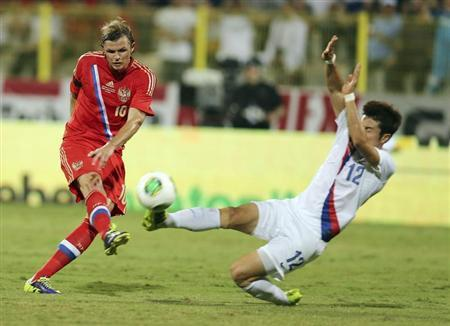 Park of South Korea fights for the ball with Tarasov of Russia during their international friendly soccer match at Al Wasl Stadium in Dubai