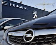 An Opel car, in front, is offered for sale by a Peugeot dealer in Gelsenkirchen, Germany, Tuesday, Feb. 14, 2017. France's PSA Group, maker of Peugeot and Citroen cars, says it's exploring a takeover of Opel, General Motors' money-losing European business. (AP Photo/Martin Meissner)