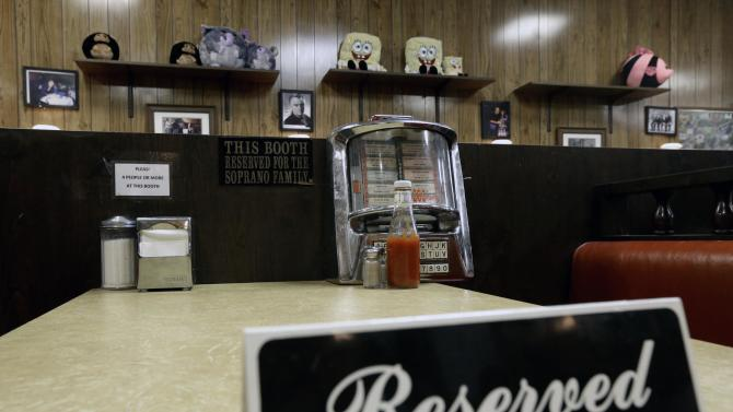 "A reserved sign sits on the booth where the last show of the HBO series ""The Sopranos"" was filmed at Holsten's ice cream parlor, Wednesday, June 19, 2013, in Bloomfield, N.J. The sign was put on the booth where the last scene was filmed in honor of actor James Gandolfini who died Wednesday in Italy. He was 51. (AP Photo/Julio Cortez)"