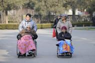Two elderly people are seen on their wheelchairs at a park in Beijing, on December 11, 2012. China's elderly face increasing uncertainty three decades since the one-child policy took hold, with no real social safety net, the law has left four grandparents and two parents with one caretaker for old age -- and bereaved families with none.