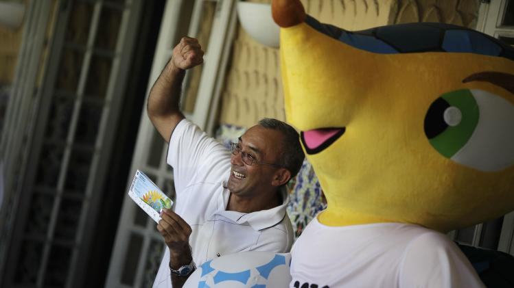 A soccer fan poses with his FIFA 2014 World Cup tickets and mascot Fuleco the Armadillo in Rio de Janeiro
