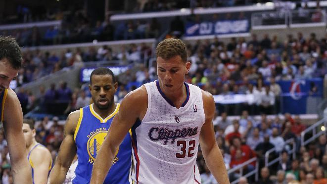 Los Angeles Clippers' Blake Griffin, top, looks down after drawing a foul from Golden State Warriors Stephen Curry, on floor, while Warriors' Andre Iguodala comes to help Curry up during the second half of an NBA basketball game in Los Angeles, Wednesday, March 12, 2014