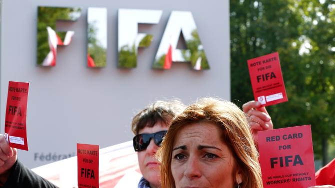 Members of the Swiss UNIA workers union display red cards during a protest in front of the headquarters of soccer's international governing body FIFA in Zurich