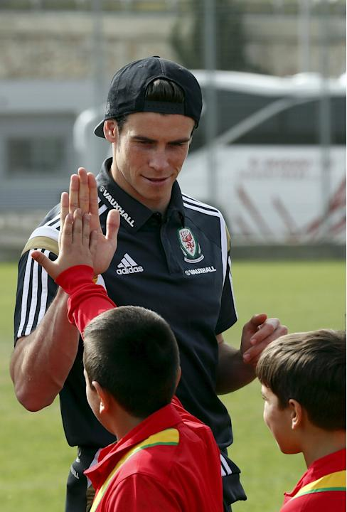 Wales' Gareth Bale high fives a boy during a kick about with Jewish and Arab children in the northern city of Haifa