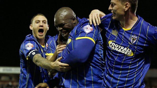 AFC Wimbledon's Adebayo Akinfenwa (C) celebrates with team-mates after scoring a goal during their FA Cup third round soccer match against Liverpool